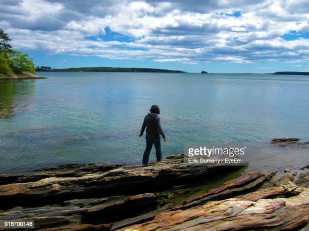 Rear View Of Man Standing At Shore Against Sky