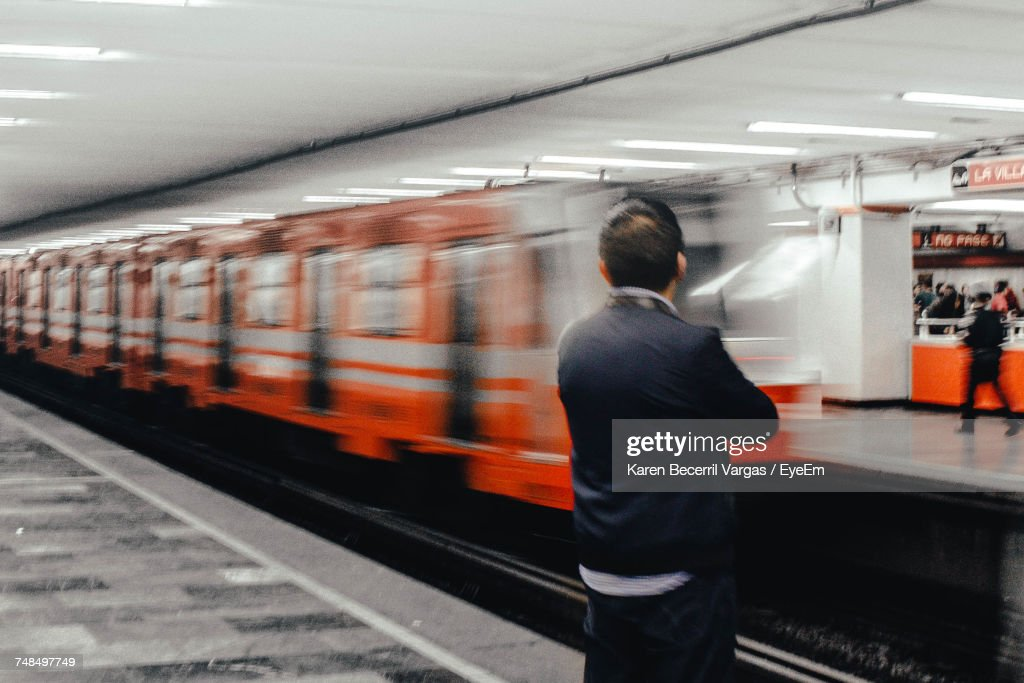 Rear View Of Man Standing At Subway Station : Stock Photo