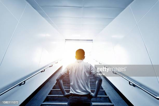 rear view of man standing at the staircases - steps stock pictures, royalty-free photos & images