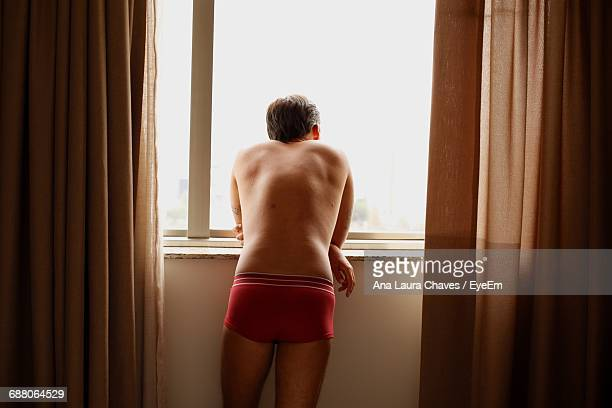 rear view of man standing at window - boxershort stock pictures, royalty-free photos & images
