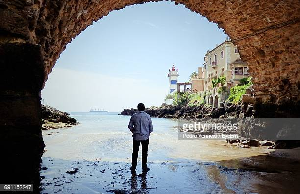 rear view of man standing below arch at beach against sky - cascais stock photos and pictures