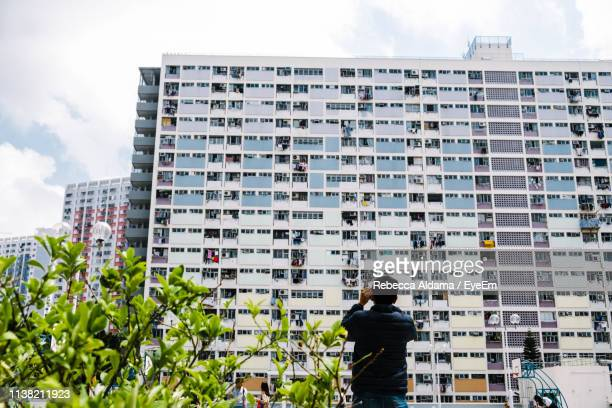 Rear View Of Man Standing By Buildings In City