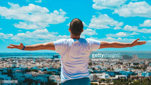 rear view of man standing by cityscape against sky - tunis stock pictures, royalty-free photos & images