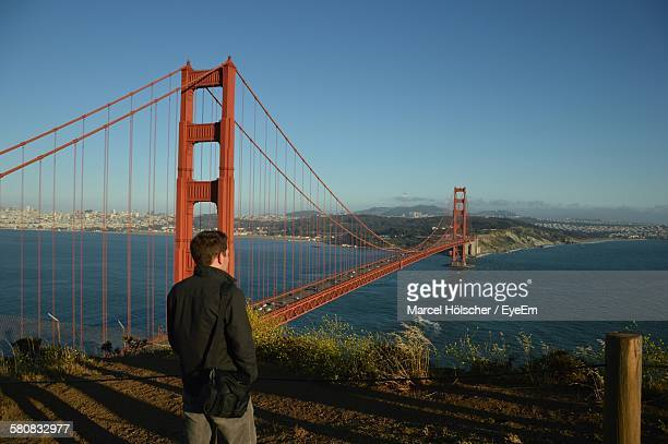 Rear View Of Man Standing By Golden Gate Bridge Over San Francisco Bay