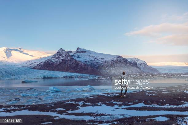 rear view of man standing by lake against snowcapped mountains - island stock-fotos und bilder