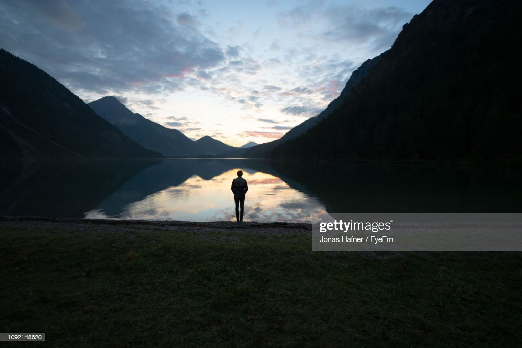 Rear View Of Man Standing By Lake Amidst Mountains During Sunset : Stock Photo