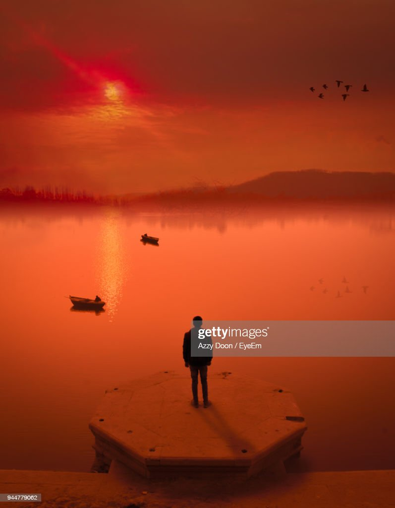 Rear View Of Man Standing By Lake During Sunset : Stock Photo