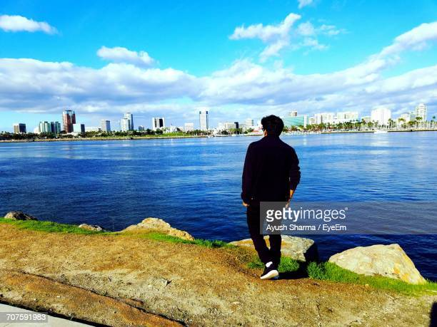 Rear View Of Man Standing By River Against City