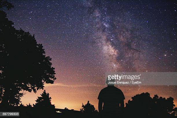 Rear View Of Man Standing By Silhouette Trees Against Star Field In Sky