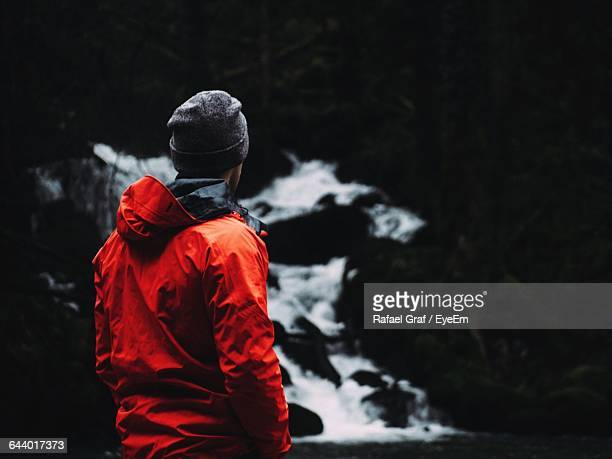 Rear View Of Man Standing By Waterfall At Forest