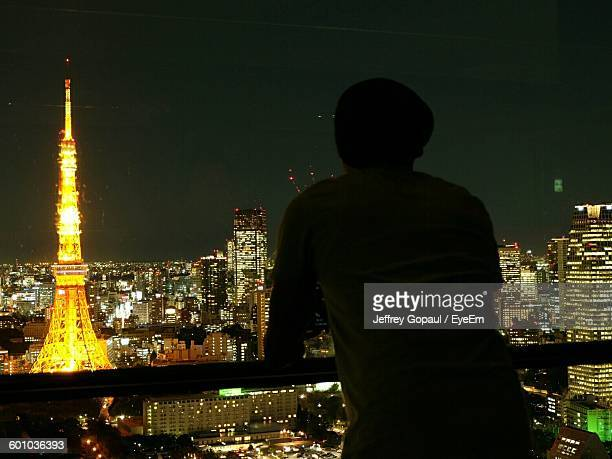 Rear View Of Man Standing In Balcony Against Tokyo Tower And Cityscape At Night