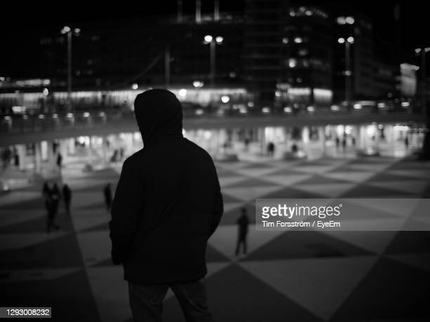 rear view of man standing in city at night - stockholm stock pictures, royalty-free photos & images