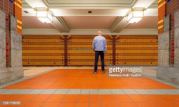 rear view of man standing in corridor of building - berlin stock pictures, royalty-free photos & images