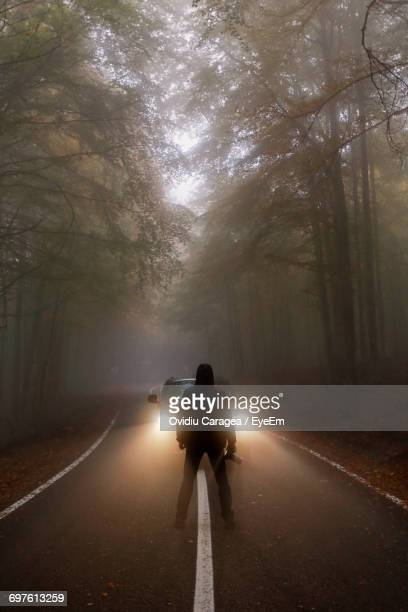 Rear View Of Man Standing In Front Of Car On Road At Forest During Foggy Weather
