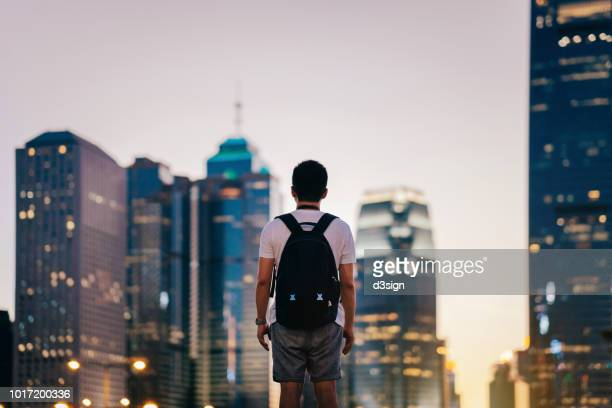 rear view of man standing in front of illuminated city skyline of hong kong at dusk - front view photos et images de collection