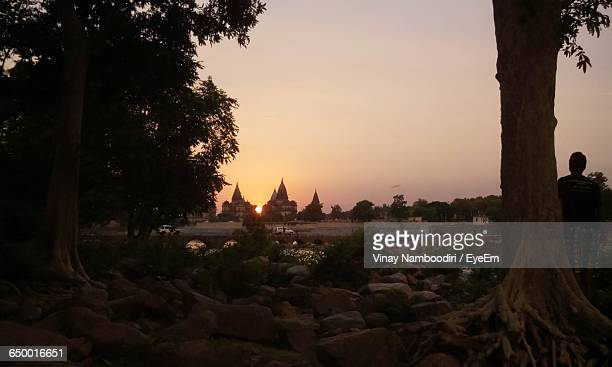Rear View Of Man Standing In Front Of Orchha Temple During Sunset