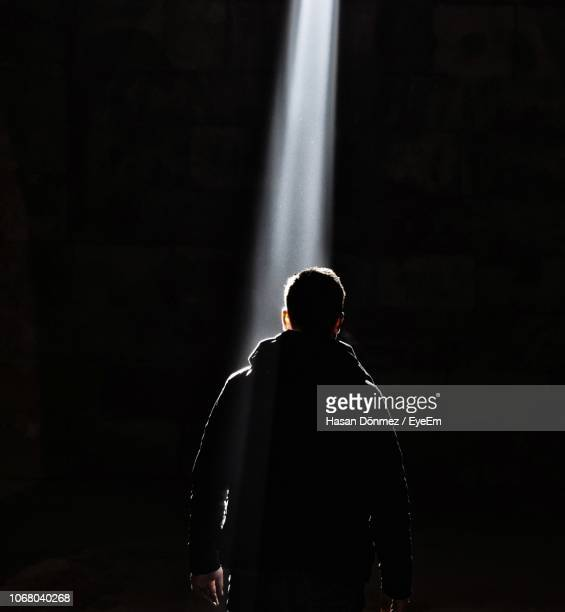 rear view of man standing in illuminated room - spotlit stock pictures, royalty-free photos & images
