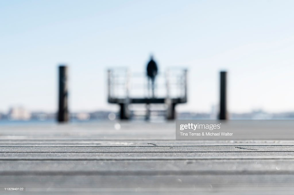 Rear view of man standing on a pier at the coast in Kiel (Germany) : Stock Photo