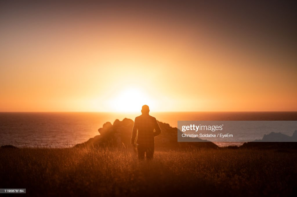 Rear View Of Man Standing On Beach Against Sky During Sunset : Stock-Foto