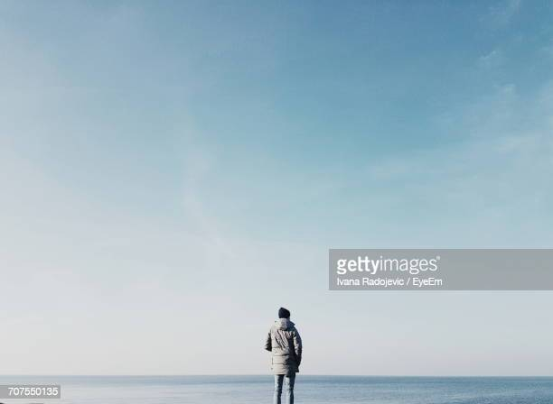 rear view of man standing on beach against sky - 無限 ストックフォトと画像