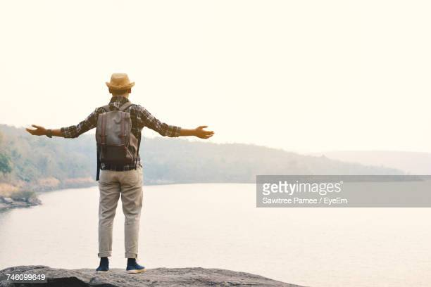 rear view of man standing on beach - arms outstretched stock pictures, royalty-free photos & images