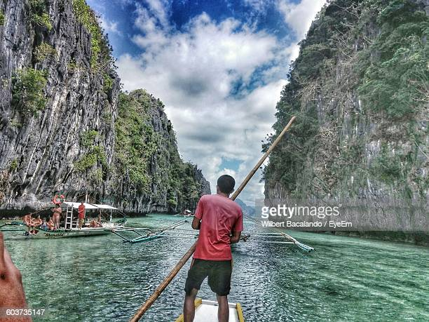 rear view of man standing on boat in sea amidst rocky cliffs at el nido - el nido stock pictures, royalty-free photos & images