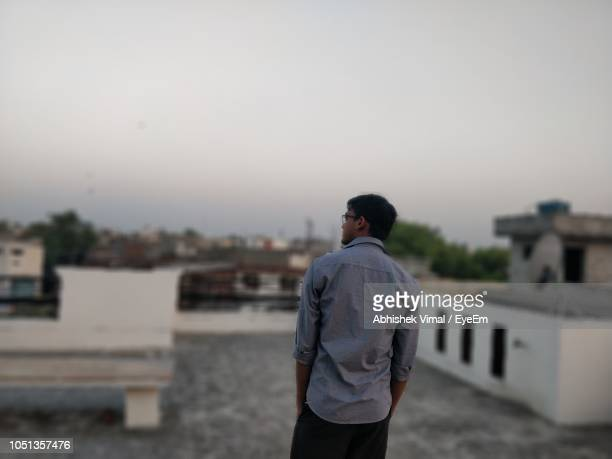 Rear View Of Man Standing On Building Terrace