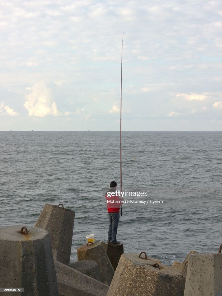 Rear View Of Man Standing On Cement Rock Fishing Against Cloudy Sky : Stock Photo