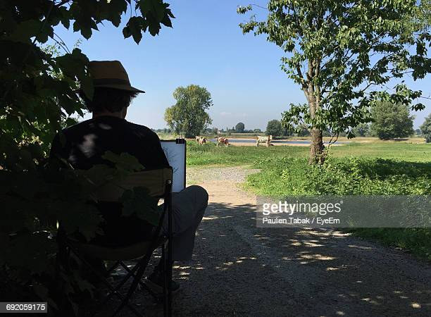 Rear View Of Man Standing On Chair At Footpath By Agricultural Field Against Clear Sky