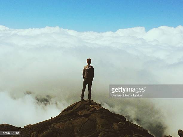rear view of man standing on cliff against cloudy sky - rocha imagens e fotografias de stock