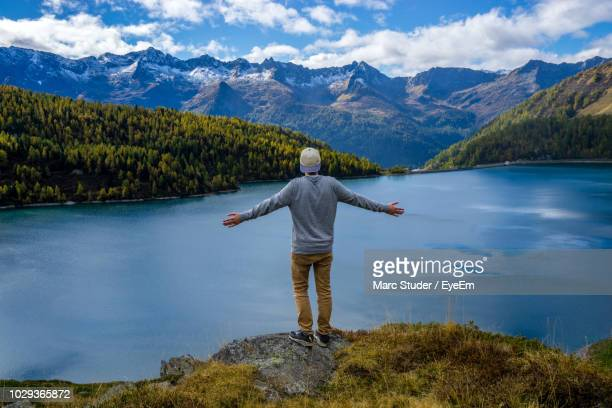 Rear View Of Man Standing On Cliff Against Lake By Mountains