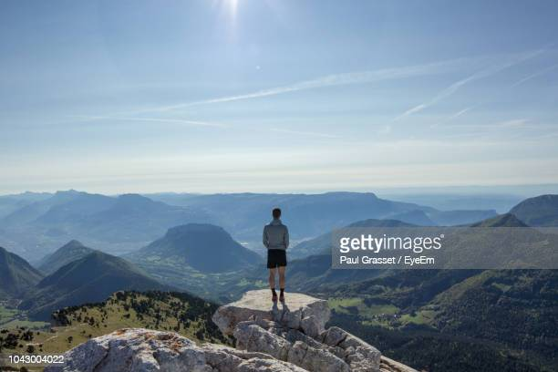 rear view of man standing on cliff against sky - grenoble stock pictures, royalty-free photos & images