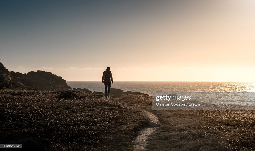 Rear View Of Man Standing On Cliff By Sea During Sunset : Stock-Foto