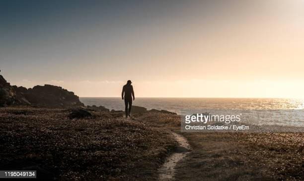 rear view of man standing on cliff by sea during sunset - christian soldatke fotografías e imágenes de stock