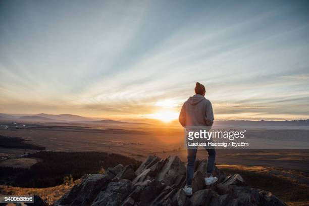 rear view of man standing on cliff - outdoor pursuit stock pictures, royalty-free photos & images
