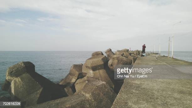 Rear View Of Man Standing On Concrete Jetty Against Sky