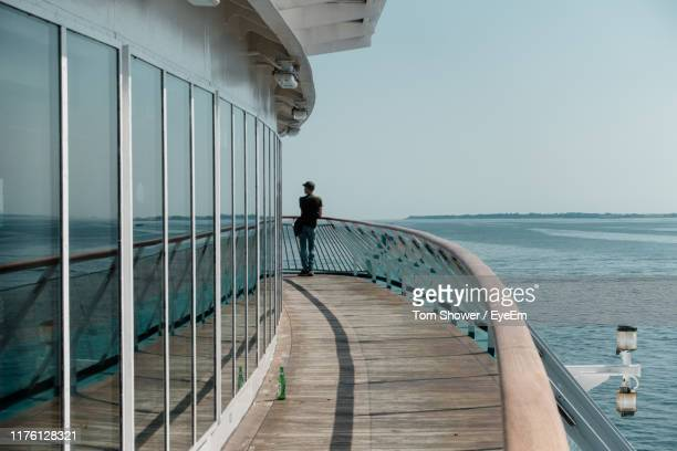 rear view of man standing on cruise ship sailing in sea - passenger craft stock pictures, royalty-free photos & images