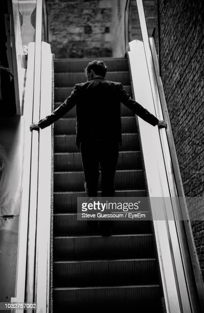 rear view of man standing on escalator - steve guessoum stockfoto's en -beelden