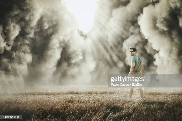 rear view of man standing on field against storm clouds - dust storm stock pictures, royalty-free photos & images