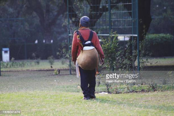 rear view of man standing on field - chandigarh stock pictures, royalty-free photos & images