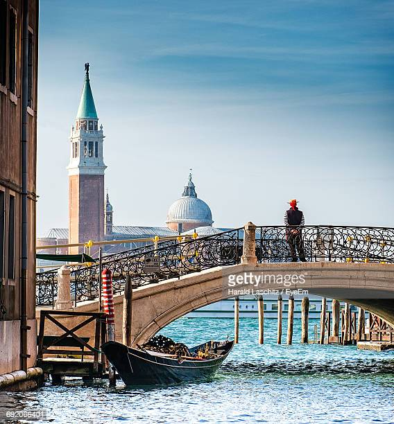 Rear View Of Man Standing On Footbridge Over Canal By Church Of San Giorgio Maggiore