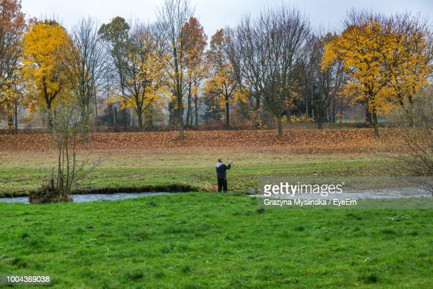 Rear View Of Man Standing On Grassy Field Against Trees During Autumn