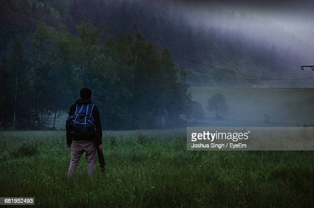 Rear View Of Man Standing On Grassy Field During Foggy Weather At Eifel