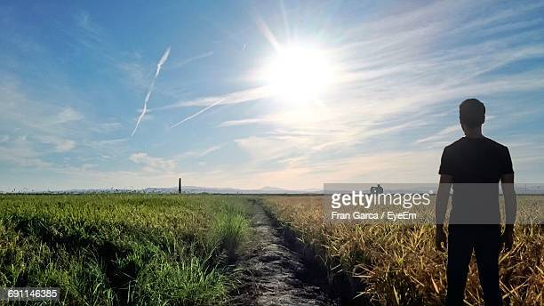 Rear View Of Man Standing On Grassy Landscape Against Sky On Sunny Day