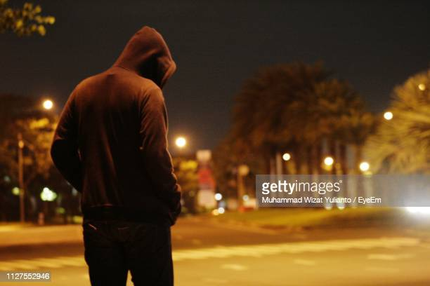 rear view of man standing on illuminated street at night - パーカー服 ストックフォトと画像
