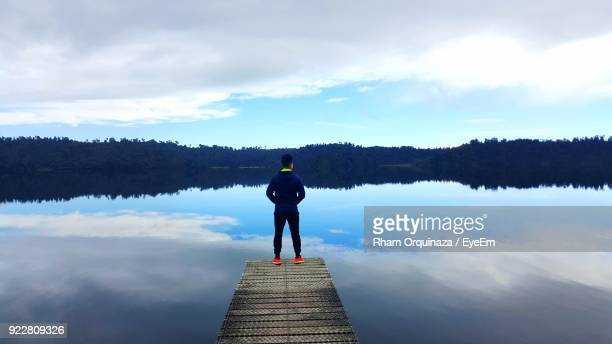 Rear View Of Man Standing On Jetty Over Lake Against Sky