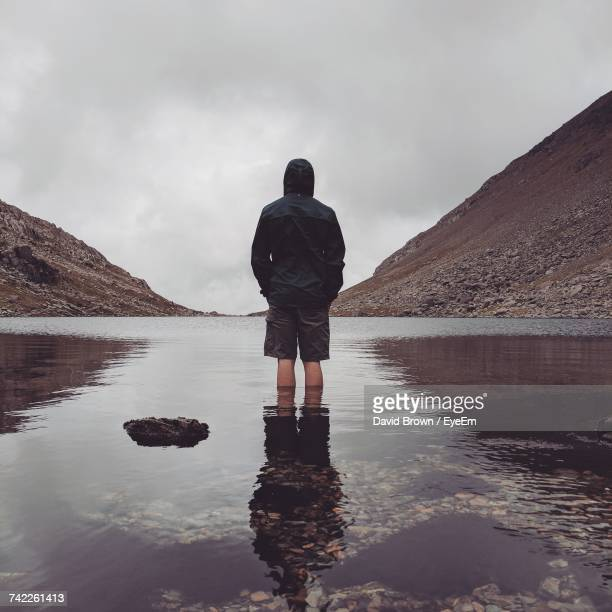 rear view of man standing on lake against sky - hands in pockets stock photos and pictures