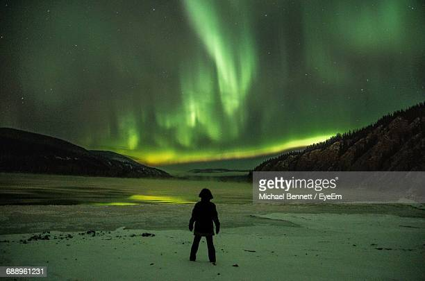Rear View Of Man Standing On Landscape Against Sky At Night