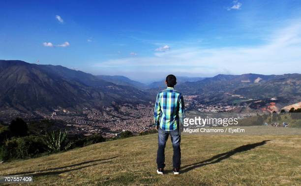 Rear View Of Man Standing On Landscape Against Sky