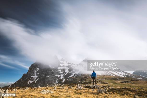 rear view of man standing on mountain against cloudy sky - fabrizio zampetti foto e immagini stock